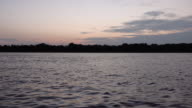 Small fisherman's dugout canoe on river under cloudy sunrise video