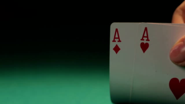 Small pile of poker chips, player has pair of aces, video