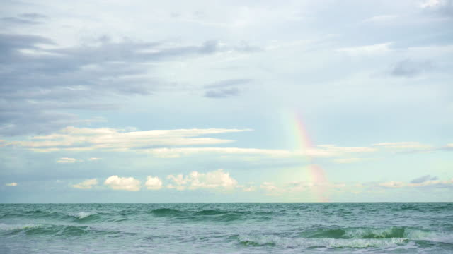 Small Rainbow in the Ocean Sea during sunset and after raining storm video