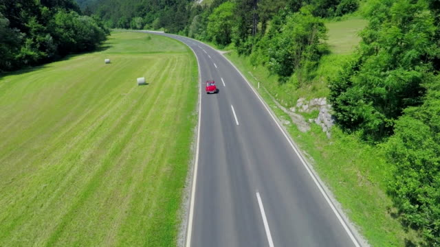 Small red car driving, motorcyclists passing by video