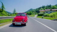 Small red vintage car passing the nearby houses video