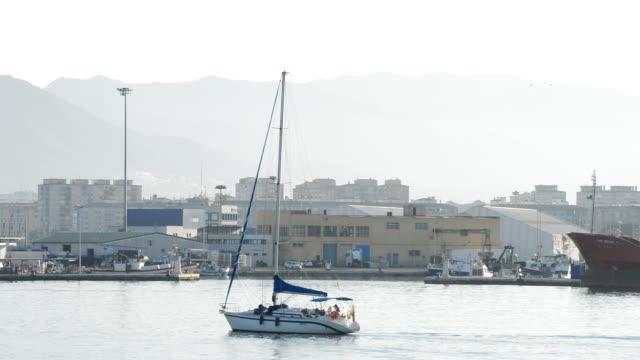 Small sailing boat navigating a harbor at sunset video