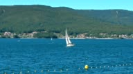 Small sailing boat with green mountain video