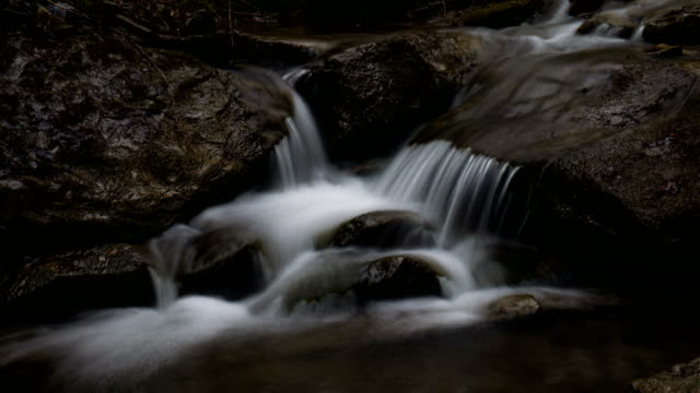 A small stream flows over rocks in time lapse video