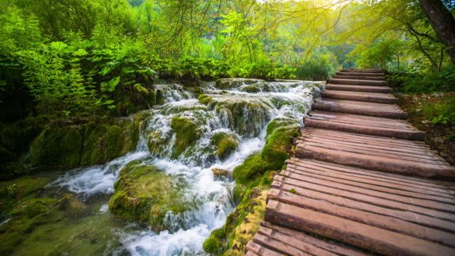STEADYCAM: Small waterfall in warm sunlight in Plitvice Lake National Park - super slow motion video