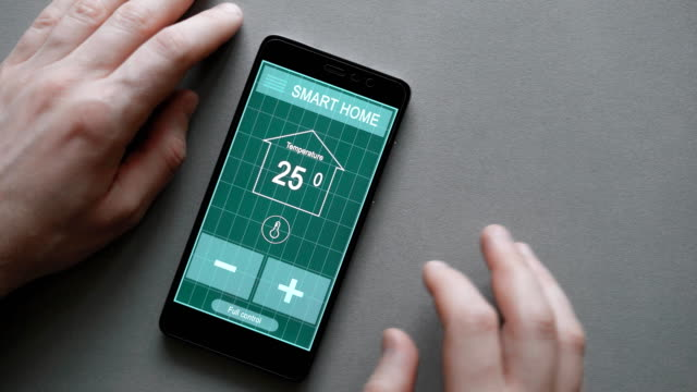 Smart House. Remote home control system on a digital tablet or phone. The smartphone lies on a neutral gray background, the texture of the kitchen table. Man controls remotely the temperature video