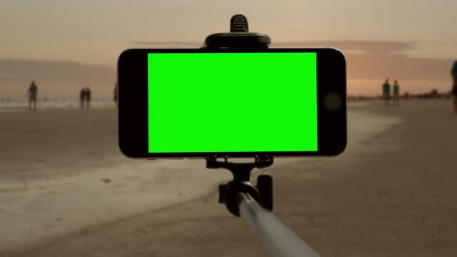 Smart phone chromakey green screen selfie stick Florida beach people video
