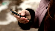 smartphone in female hands outdoors video