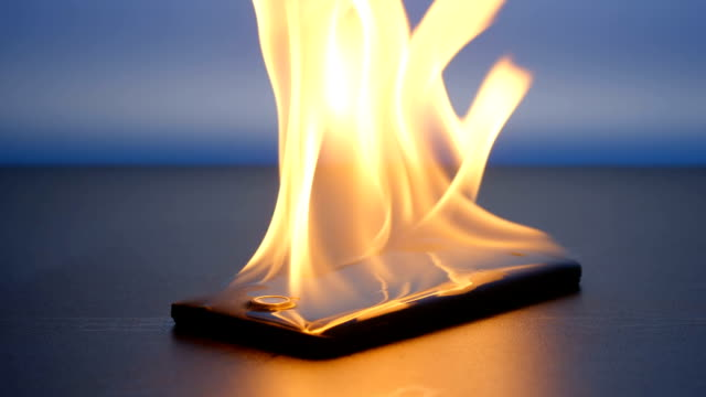 SLOW MOTION: Smartphone lies and burning on a table in the night video