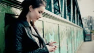 Smartphone text, girl standing by a city bridge with graffiti. video
