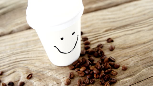 Smiley face on disposable cup with coffee beans on sack video