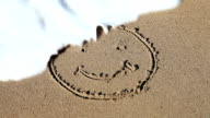 Smiley face sign on the beach sand video