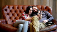 smiley young couple sitting on sofa and taking a selfie picture by the smartphone video