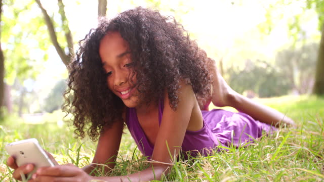 Smiling Afro girl in the park on the phone video