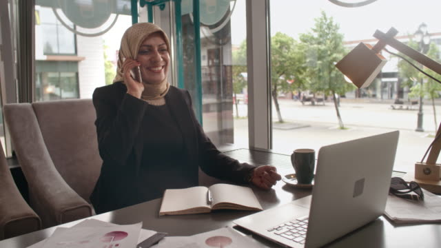 Smiling Arab businesswoman talking on phone in cafe video