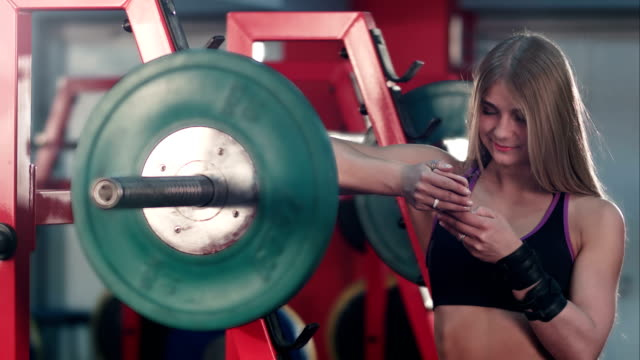 Smiling athletic woman messaging on her phone in the gym video