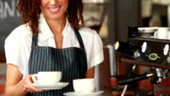 Smiling barista handing two cups of coffee video