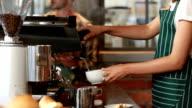 Smiling barista serving a client video
