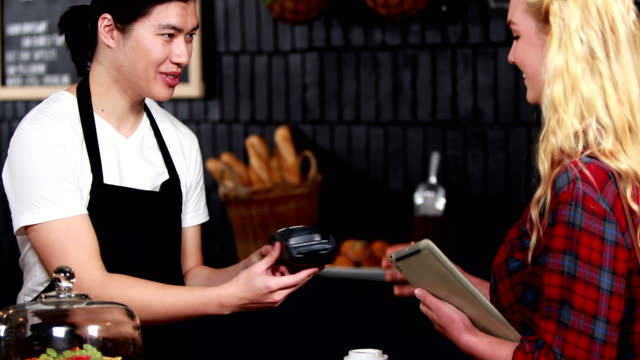 Smiling barista taking credit card from customer video