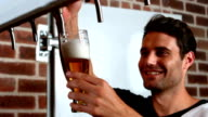 Smiling barman pulling a pint of beer video