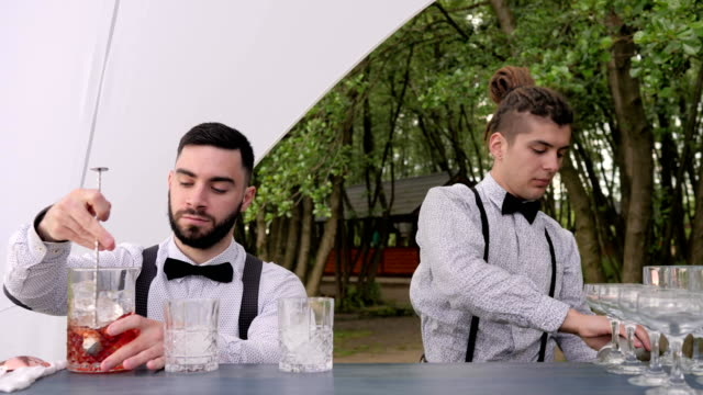 smiling bartenders behind bar, barman stir spoonful ice in glass, bartender pouring cocktail from shaker into mixing glass video