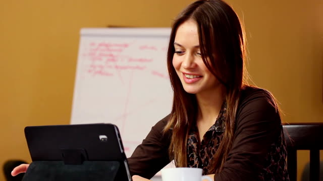 Smiling beautiful attractive young woman reads tablet PC office video