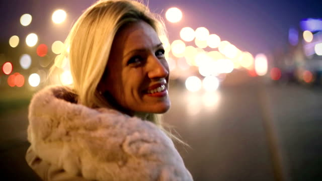 Smiling blond woman walking the street. video