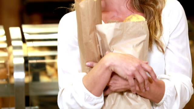 Smiling blonde holding paper bags video