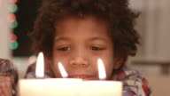 Smiling boy looks at candle. video