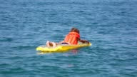 Smiling boy oaring on inflatable mattress in sea video