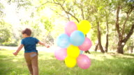 Smiling boy running in park with balloons slow motion video