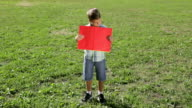 Smiling boy standing with empty blank banner video