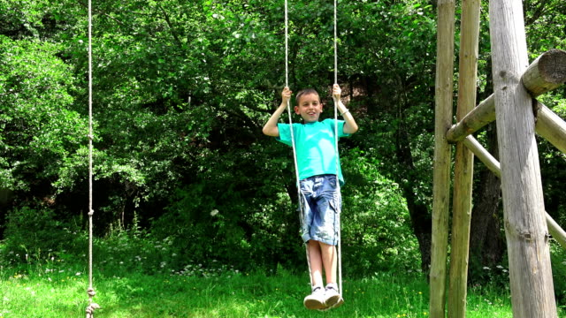 Smiling boy swinging on a rope at a playground video