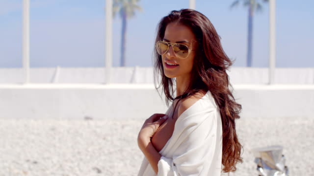 Smiling Brunette Woman Wearing Sunglasses on Beach video