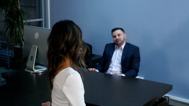 Smiling business man talking with his colleague during an informal meeting at office video