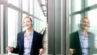 Smiling businesswoman listening to music and dancing using headphones video