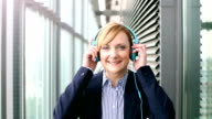 Smiling businesswoman putting on headphones and starts dancing video