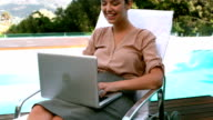 Smiling businesswoman using laptop poolside video