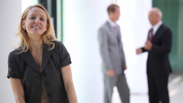 smiling businesswoman with blurred men in back video