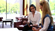 Smiling businesswomen having a meeting using tablet pc video