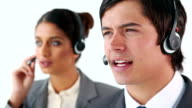 Smiling call centre agents using headsets video