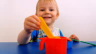 Smiling child playing with toy dishes video
