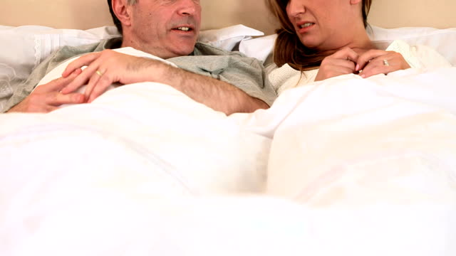 Smiling couple chatting and lying in bed video