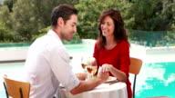 Smiling couple having dinner poolside video