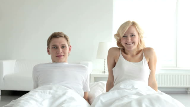 Smiling couple in bed video