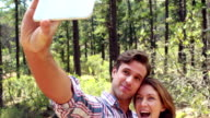 Smiling couple on a hike taking a selfie video