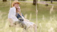 SLO MO DS Smiling couple relaxing on a swing video