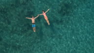 AERIAL: Smiling couple swimming in sea, floating on water surface holding hands video