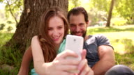 Smiling couple taking selfie on their phone in a park video