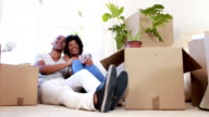 Smiling couple unpacking cardboard boxes video